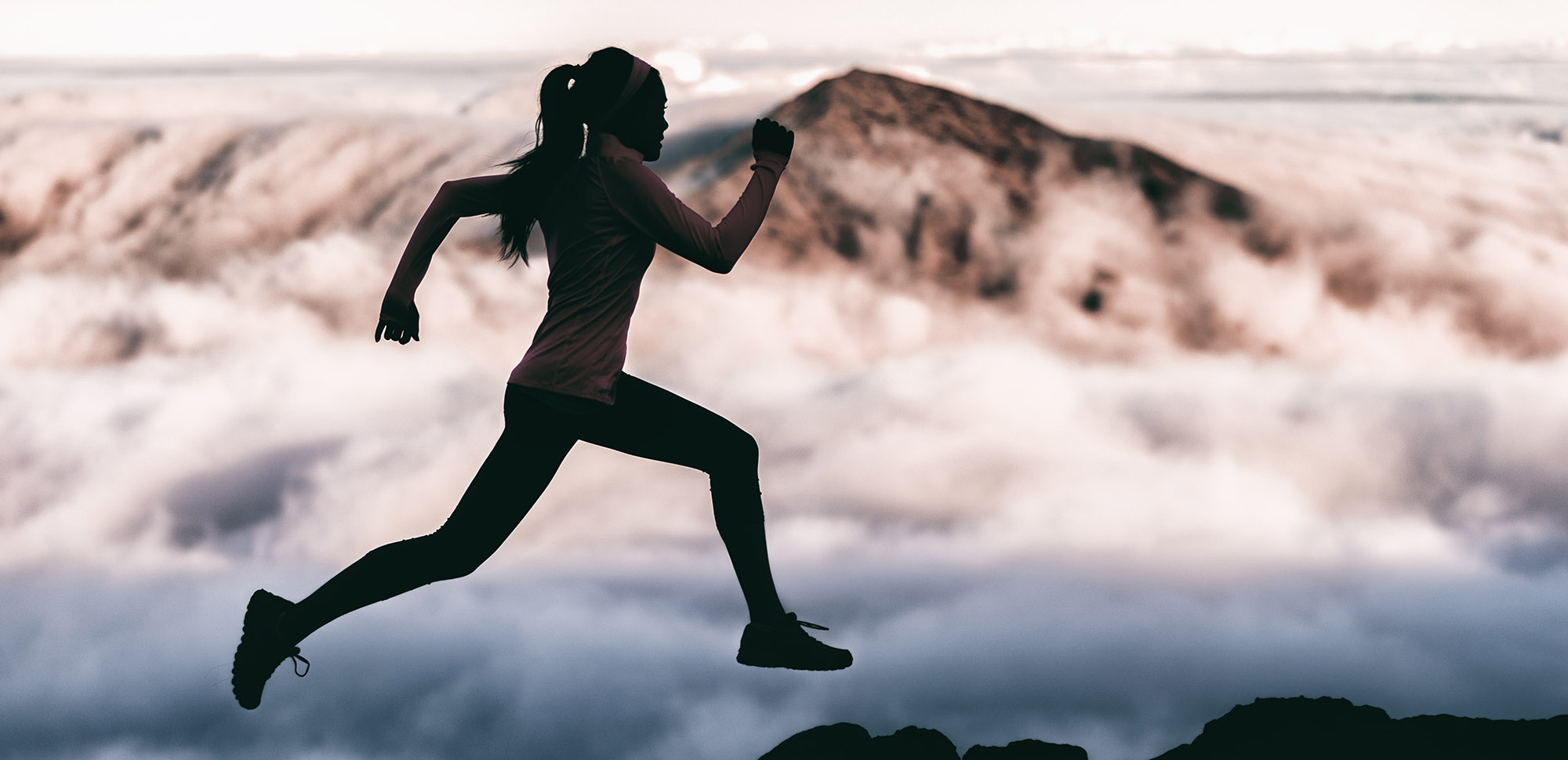 woman running atop a mountain with clouds in the background