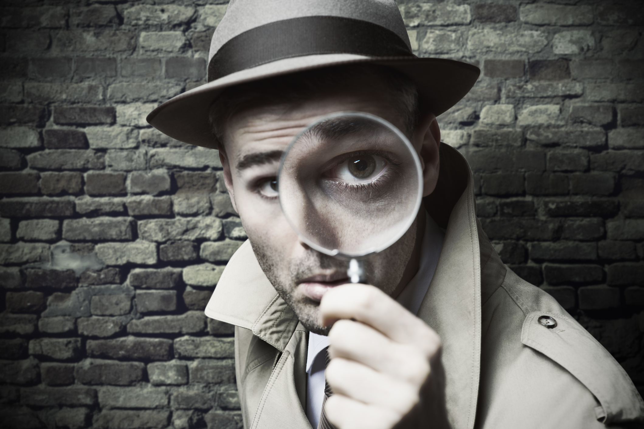 picture of a detective looking through a magnifying glass